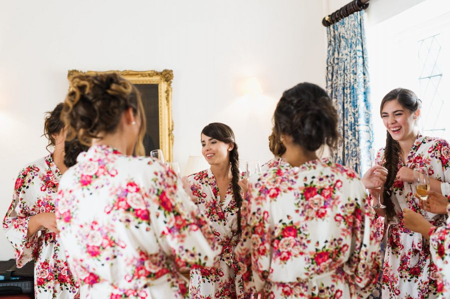 Bridal prep of Bride and her bridesmaids laughing in floral dressing gowns Weston on the Green Manor