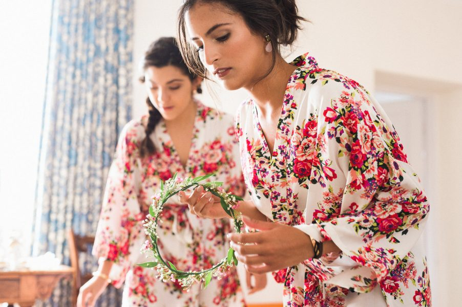 Bridal prep of bridesmaids inspecting the flowers from Fabulous Flowers in red floral dressing gowns Weston on the Green Manor