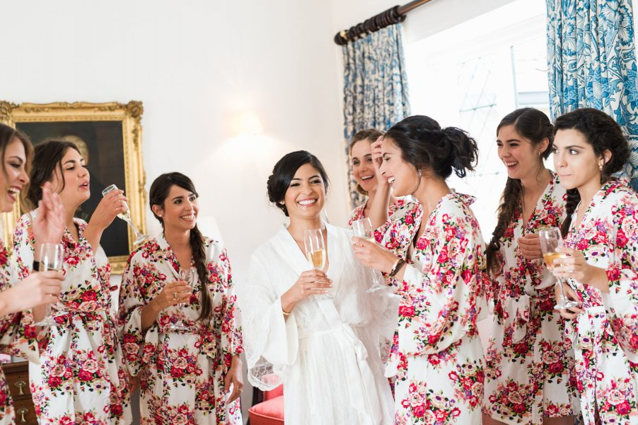 Bridal prep of Bride and her bridesmaids laughing in red floral dressing gowns Weston on the Green Manor