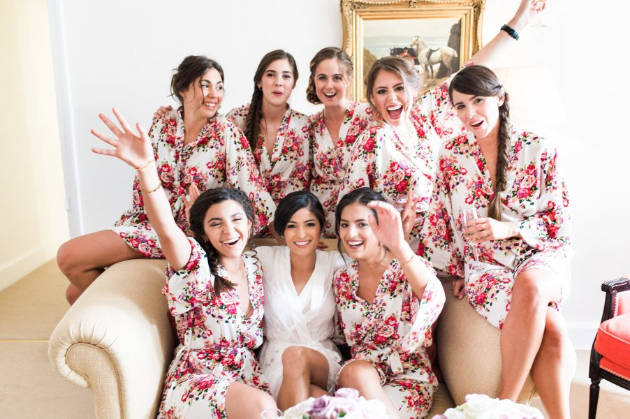 Bridal prep of bridesmaids cheering around the Bride on a sofa dressed in red floral dressing gowns Weston on the Green Manor