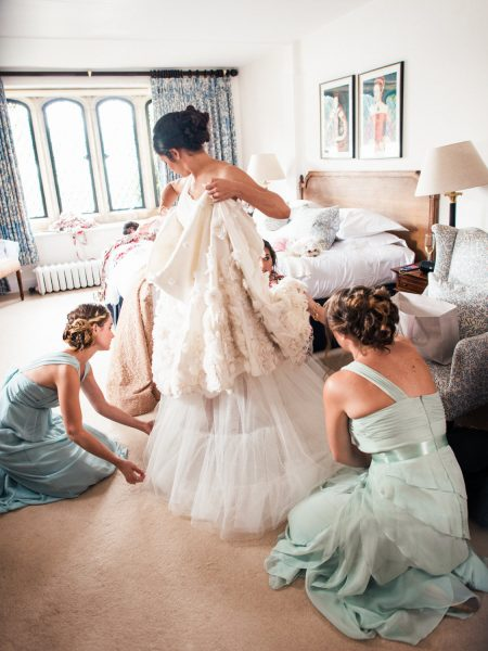 Bridal prep of bride stepping into her Temperley wedding dress surrounded by bridesmaids in pastel dresses Weston on the Green Manor