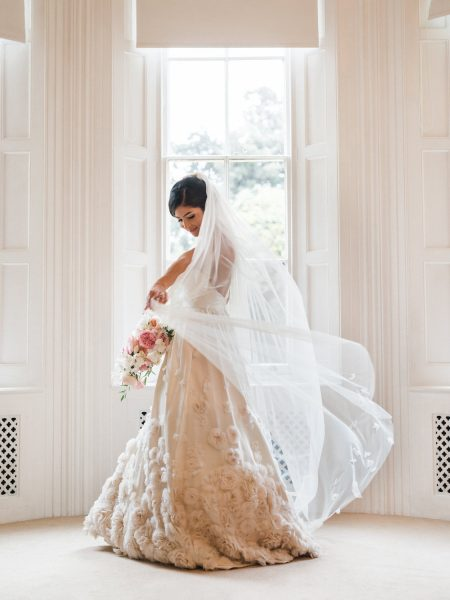 Portrait of Bride in Temperley wedding dress waving flowing veil in front of window Weston on the Green Manor