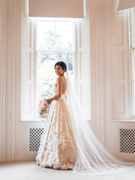 Portrait of Bride in Temperley wedding dress with trailing veil in front of window Weston on the Green Manor