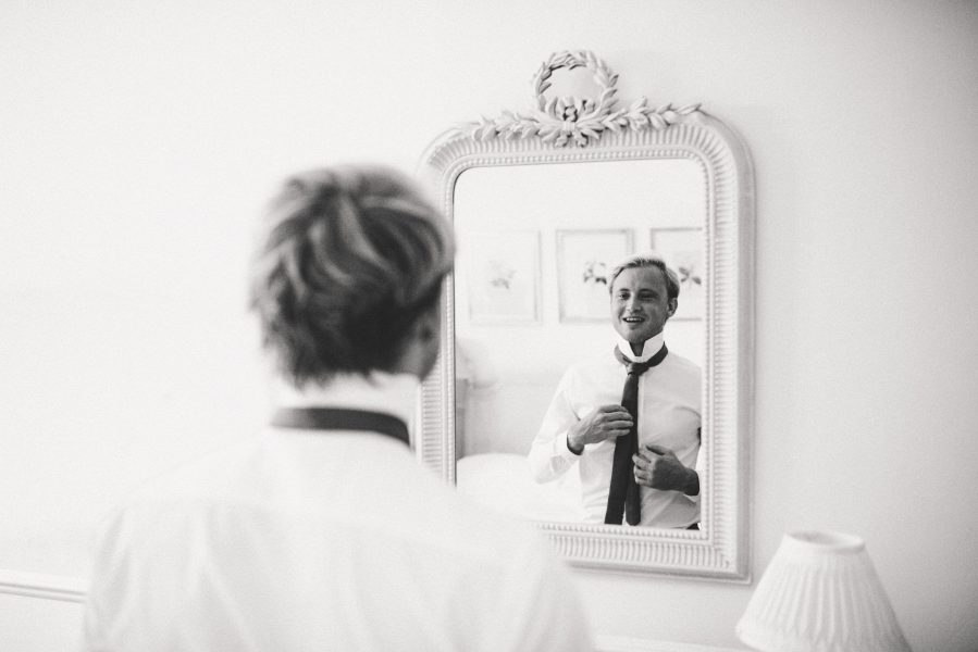 Groom adjusting tie in French style mirror Weston on the Green Manor