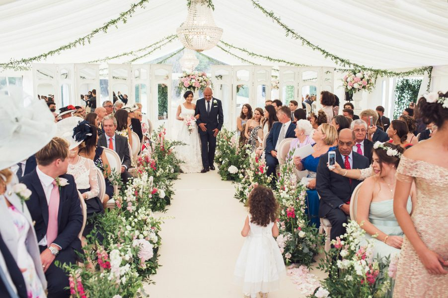 Bride and father of the Bride walk down aisle adorned by flowers of marquee Weston on the Green Oxfordshire