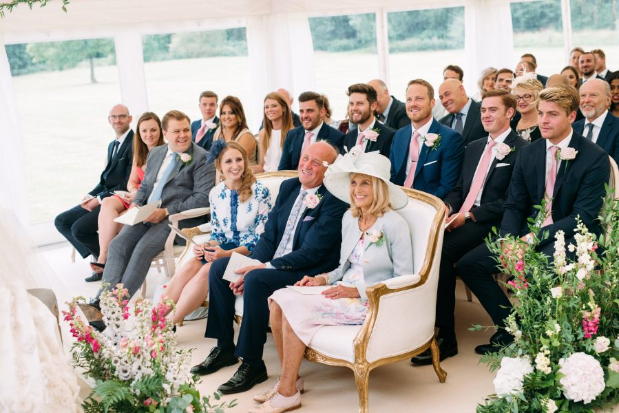 Mother of the Groom and Father of the Groom smiling in front row of ceremony at Weston on the Green Oxfordshire