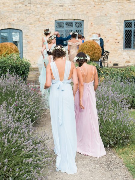 Bridesmaids wearing assorted pastel dresses exiting ceremony walking through lavender at Weston on the Green Manor Oxfordshire