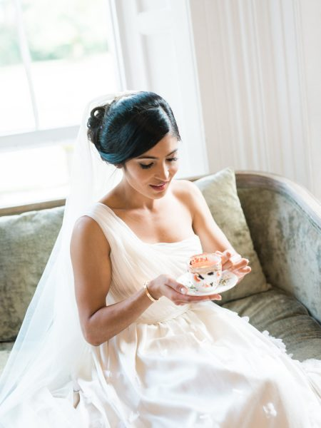 Bride sips Pimms out of a vintage teacup at Weston on the Green Manor Oxfordshire