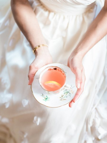 Close up of Pimms in a of a vintage teacup held by Bride at at Weston on the Green Manor Oxfordshire
