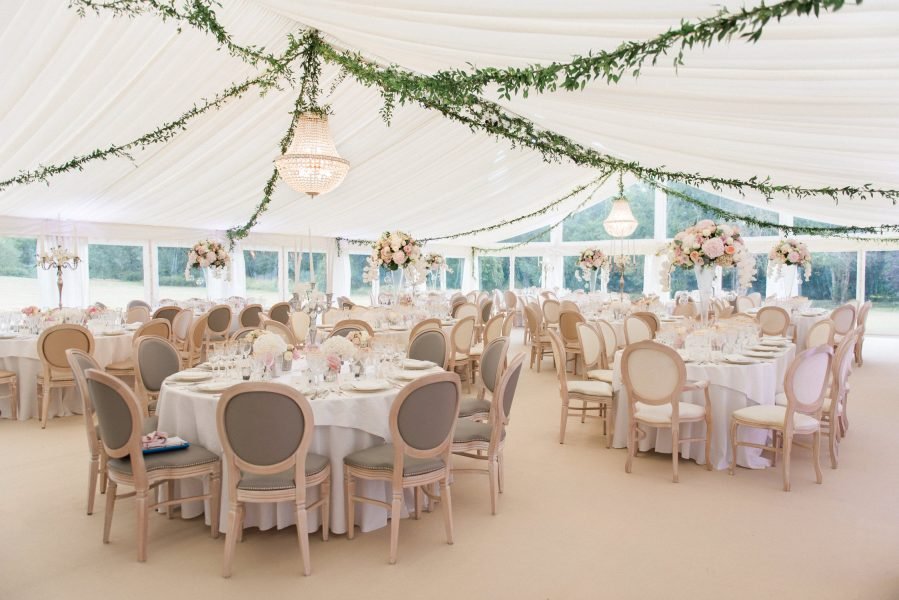 Elegant wide shot of marquee tables and chandelier in marquee at Weston on the Green Oxfordshire