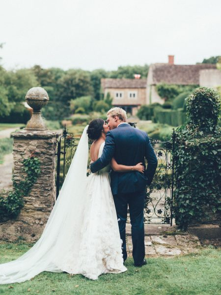 Bride in Temperley and Groom kiss in front of topiary garden in the grounds of Weston on the Green Manor Oxfordshire