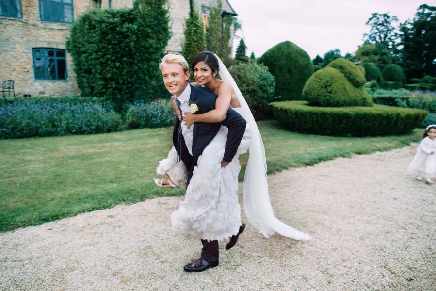 Candid moment of Groom giving Bride in Temperley dress a piggy back in the grounds of Weston on the Green Manor Oxfordshire