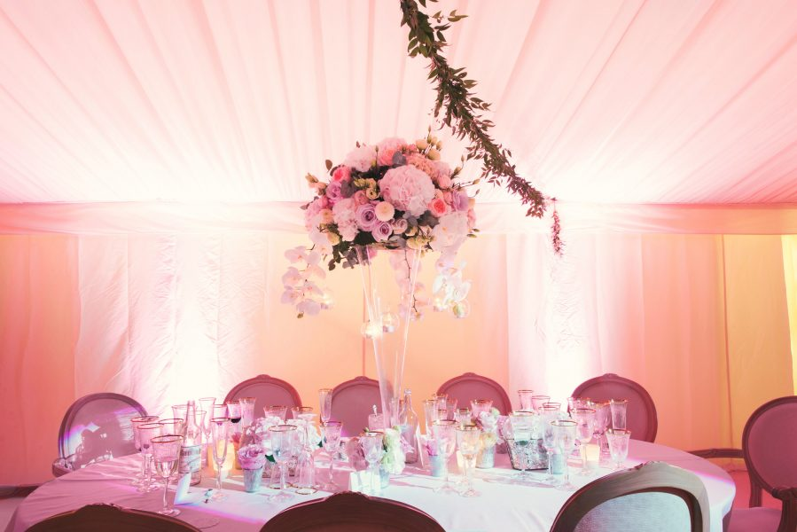 Table decor including flowers and evening uplighting in pinks and purples in the marquee at Weston n the Green Oxfordshire